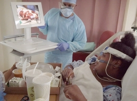 Mother sees newborn baby on video screen with doctor